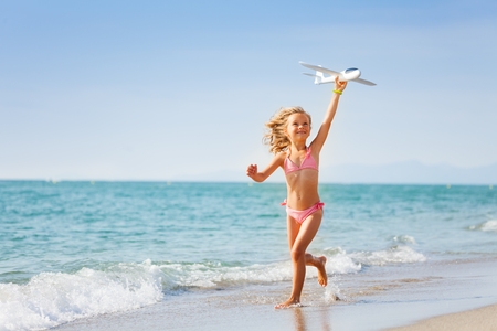 Cute six years old girl in pink swimsuit holding toy plane and running on the beach in summer