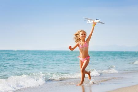 linda niña de seis años en traje de baño de color rosa que sostiene el avión de juguete y que se ejecuta en la playa en verano