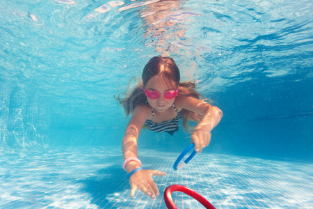 Preteen girl in pink goggles training under water