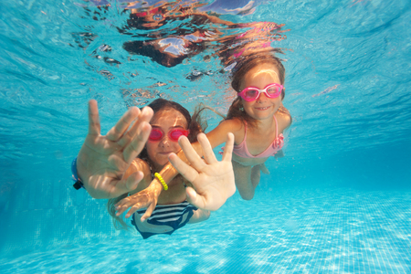 resort life: Two happy girls swimming under clear water of pool Stock Photo