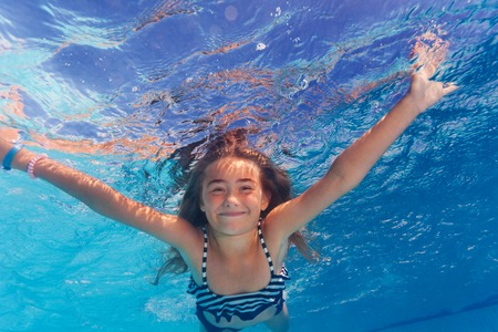 Beautiful preteen girl enjoying swimming under water of the pool