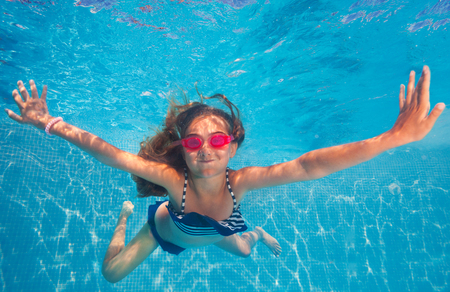Happy girl wearing pink goggles, holding breath, swimming under water of pool