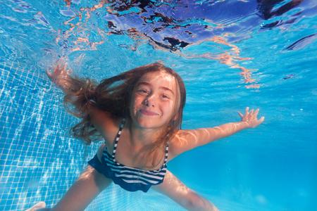 スイミングプールの澄んだ水の下でダイビングかわいい女の子の水中撮影