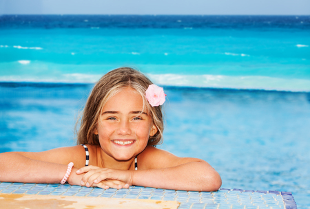 Portrait of smiling preteen girl with pink flower in her hair, resting on the edge of swimming pool