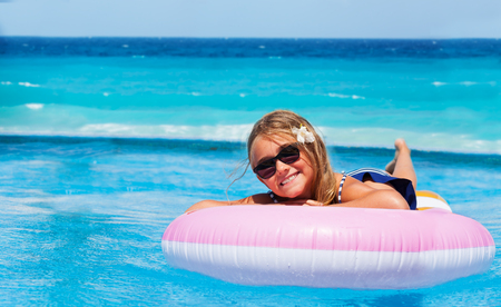 Portrait of preteen blond girl in sunglasses, enjoying summer vacation, swimming on pink inflatable mattress Stockfoto - 106037077