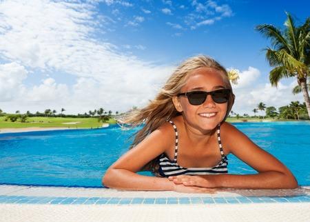 Portrait of happy preteen girl in sunglasses, sunbathing in the outdoor swimming pool in summer