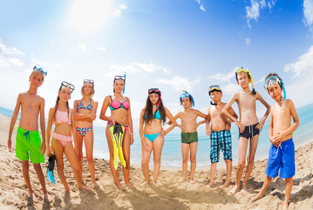 Group of kids in swimsuits standing on sandy beach
