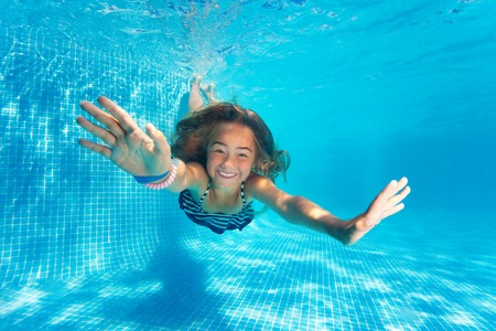 Portrait of preteen girl diving with fun in pool Фото со стока