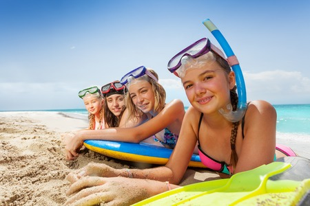 Cute girls laying with body boards on sandy beach