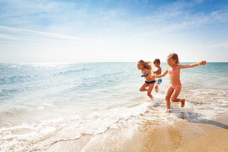 여름에 바다의 가장자리를 따라 달리는 행복한 친구들 스톡 콘텐츠 - 89273129