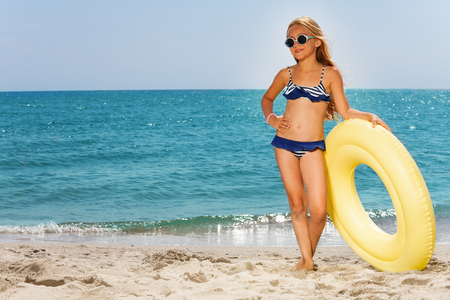 Weinig strandmodel poseren met gele rubberen ring