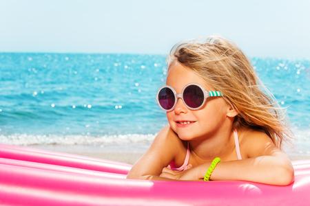 Meisje om te zonnebaden op opblaasbare lounge aan zee