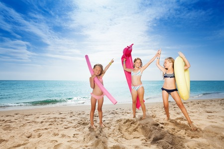 Happy girls with swimming tools on sandy beach