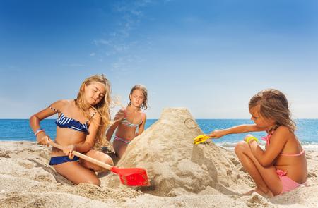 Drie gelukkige meisjesvrienden die zandkasteel beeldhouwen Stockfoto