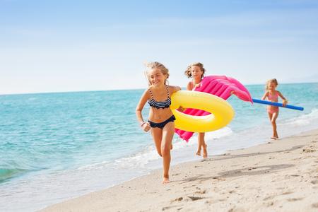 Joyful girls in swimwear running at tropical beach Stock Photo