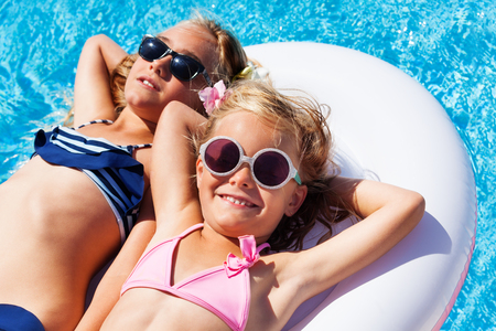 Top view portrait of two age-diverse girls, happy friends, wearing bikini and sunglasses, relaxing on pink mattress in swimming pool