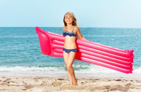 Gelukkig meisje met opblaasbare matras op wit strand Stockfoto