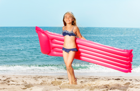 Happy girl with inflatable mattress on white beach