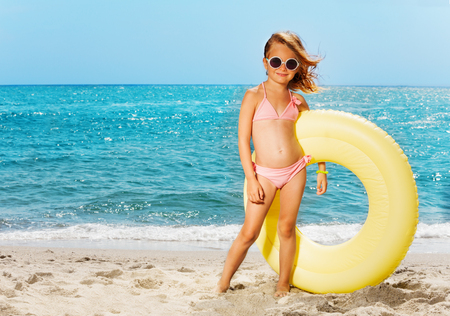Little girl with big rubber ring on the beach