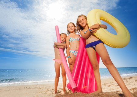 Funny girls with colorful swimming tools on beach Stock fotó