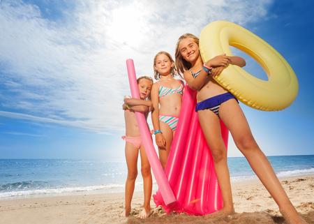 Lustige Mädchen mit bunten Schwimmgeräten am Strand Standard-Bild - 89685285