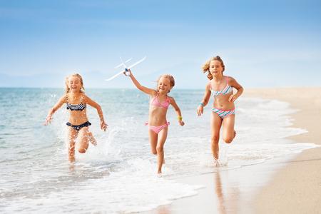 Girls running with airplane model on the seashore