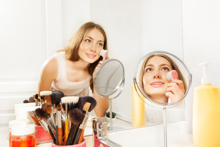 esthetics: Beautiful young woman using facial cleansing brush Stock Photo