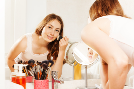 esthetics: Young woman applying makeup with face powder brush Stock Photo