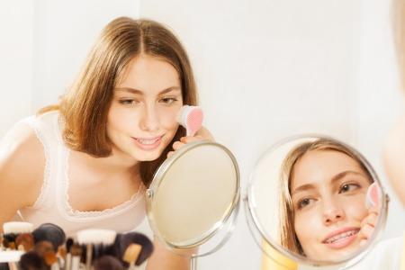 esthetics: Attractive young woman using skin-cleaning brush Stock Photo