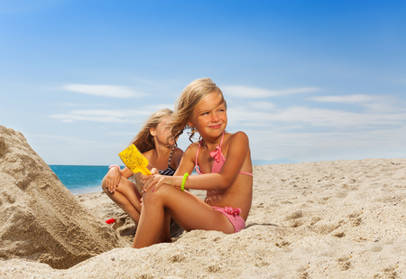 Portrait of adorable six years old girl playing with sand at the beach in summer Standard-Bild