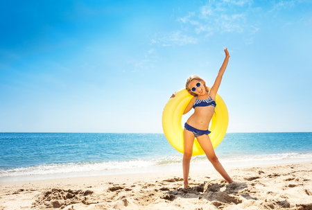 Preteen girl wearing sunglasses, holding yellow rubber ring, standing on white sand  with her back to blue sky and sea Stockfoto