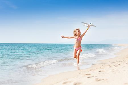 Petite fille qui court sur la côte avec un avion jouet Banque d'images - 90241847