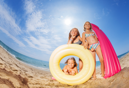 Three happy girls friends playing at sandy beach Stock Photo