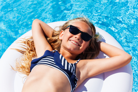 Top view portrait of preteen blond girl in bikini and sunglasses, enjoying suntan on inflatable mattress in swimming pool Foto de archivo