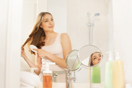 Pretty woman brushing her long hair in bathroom Stock Photo