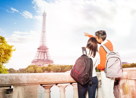 Young couple with backpacks walking along Paris 스톡 콘텐츠