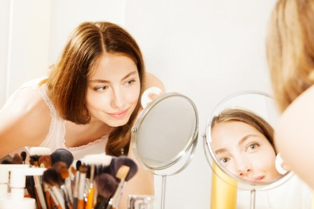 Woman cleaning face with cotton pad seen in mirror Stock Photo