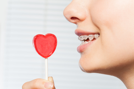 Woman profile with red lollipop in shape of heart