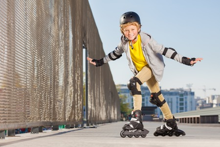 Happy boy on rollers making trick at skate park