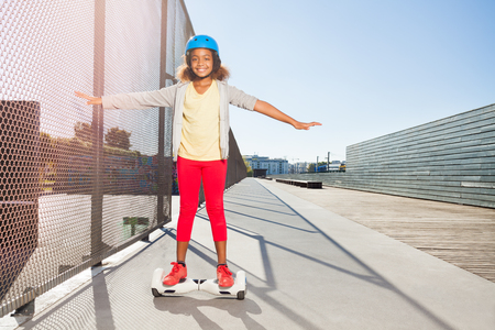 African girl riding hoverboard on the side walk Stock Photo