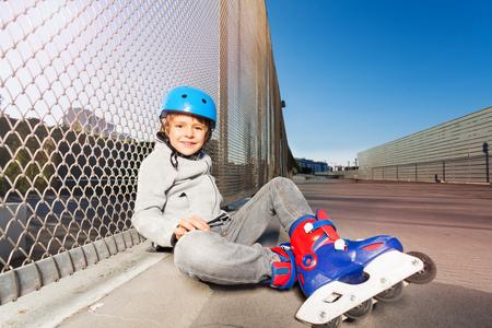 Patinador en línea sentado en el piso del parque de patinaje