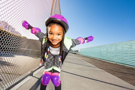 African girl in helmet rollerblading at skate park Stock Photo