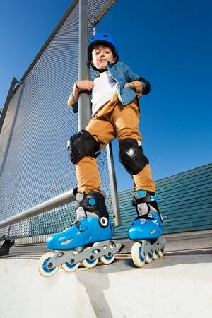 Young inline skater in helmet posing at skate park
