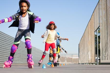 Happy girls learning forward slalom at skate park Stock Photo