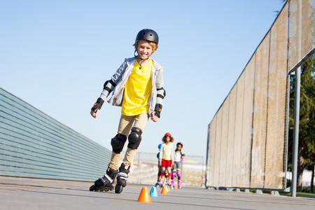 Cute boy curving around the cones at slalom course Stock Photo