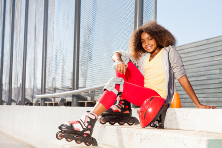 Girl sitting on the stairs in roller skates Stock Photo