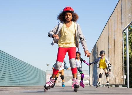 Niña africana en patines con amigos en el estadio