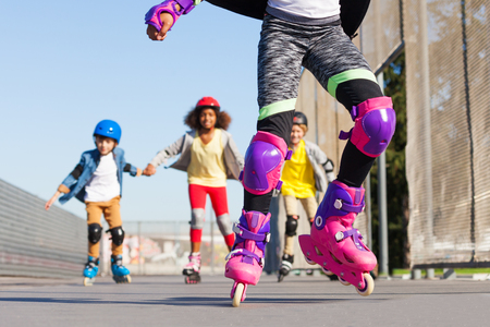 Kids rollerblading in protective gear outdoors