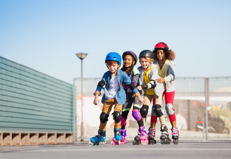 Happy kids rollerblading in a row outdoors