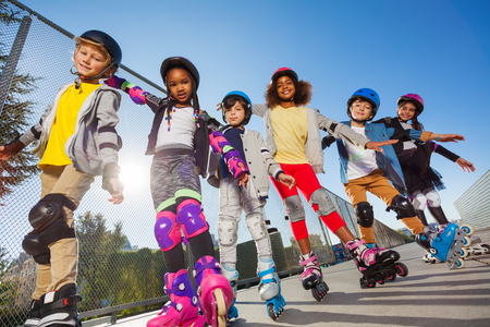 Happy kids rollerblading with hands like wings Stock Photo